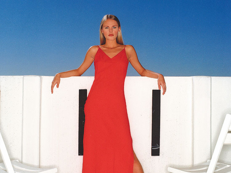 woman in a long red dress in front of a white fence