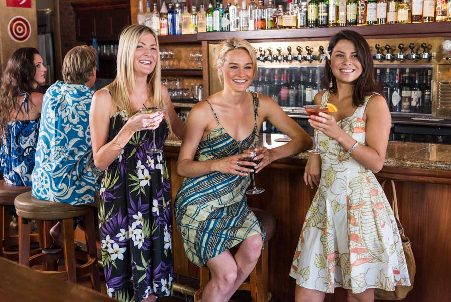 3 ladies in aloha dresses seated at a bar.